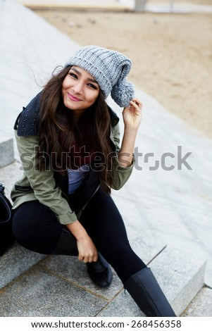 Portrait of smiling woman sitting on the steps at leisure time outdoors, cold autumn day, attractive girl on promenade on the beach - stock photo
