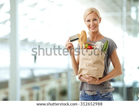 Portrait of smiling woman standing at supermarket and holding hand shopping paper bags full of food while other hand there is a credit card.  - stock photo