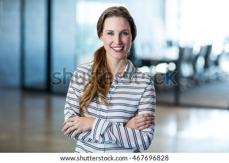 Portrait of smiling woman standing with arms crossed in office