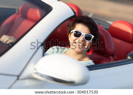 Portrait of smiling woman wearing sunglasses in a convertible sports car with red leather interior. - stock photo