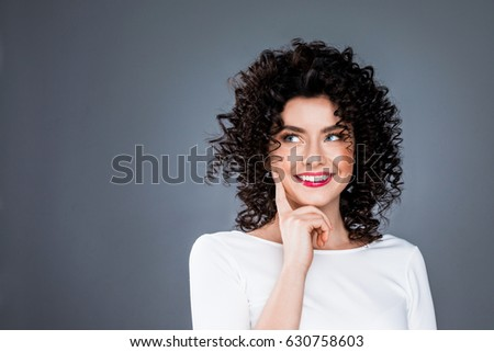 Portrait of smiling woman with finger on chin look aside thinking about something, making a choice