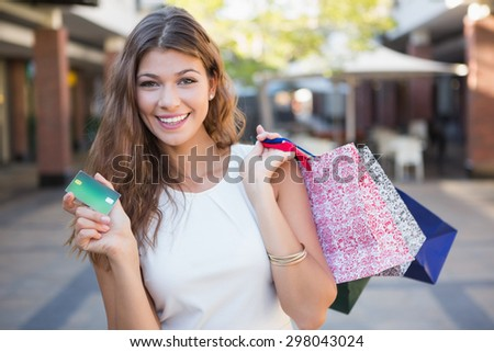 Portrait of smiling woman with shopping bags and credit card looking at camera at the shopping mall - stock photo
