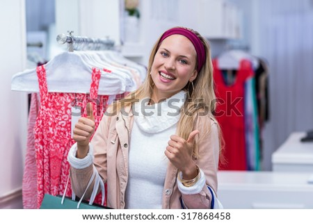 Portrait of smiling woman with shopping bags looking at camera with thumbs up in clothing store