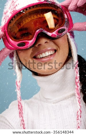 Portrait of smiling woman with ski goggles - stock photo