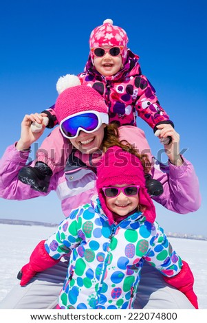 Portrait of smiling woman with two cute little girls in wintertime - stock photo