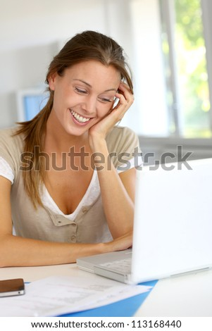 Portrait of smiling woman working on laptop at home - stock photo