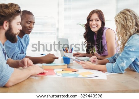 Portrait of smiling woman working with coworkers at desk in office
