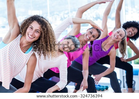 Portrait of smiling women bending with arms raised in fitness studio - stock photo