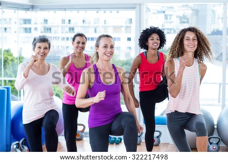 Portrait of smiling women exercising with clasped hands in fitness studio - stock photo