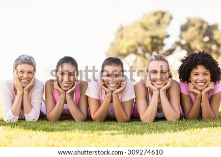 Portrait of smiling women lying in a row and wearing pink for breast cancer in parkland - stock photo