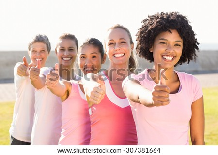 Portrait of smiling women wearing pink for breast cancer and doing thumbs up in parkland - stock photo