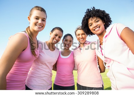 Portrait of smiling women wearing pink for breast cancer in parkland - stock photo