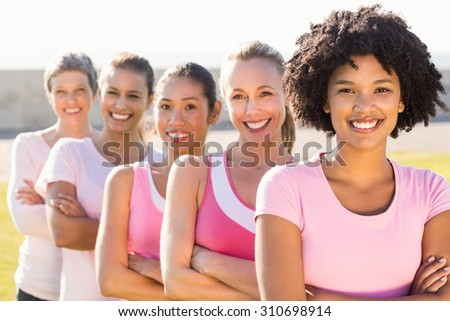 Portrait of smiling women wearing pink for breast cancer with arms crossed in parkland - stock photo
