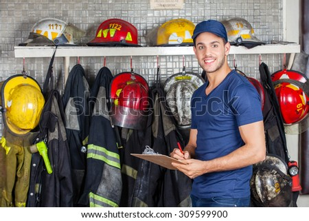 Portrait of smiling worker holding clipboard while standing against uniforms hanging at fire station - stock photo