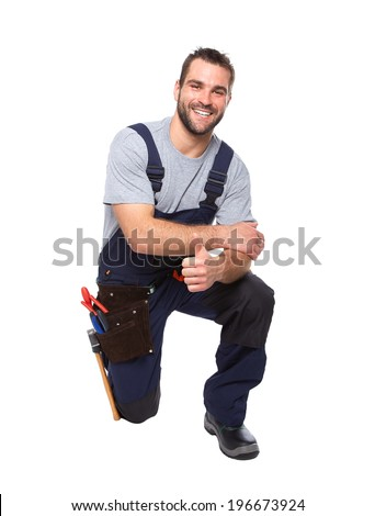 Portrait of smiling worker kneeling with hand doing ok gesture isolated on white background
