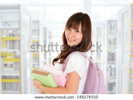 Portrait of smiling young adult Asian female student standing inside library - stock photo