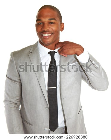Portrait of smiling young African American businessman loosing his tie over white background