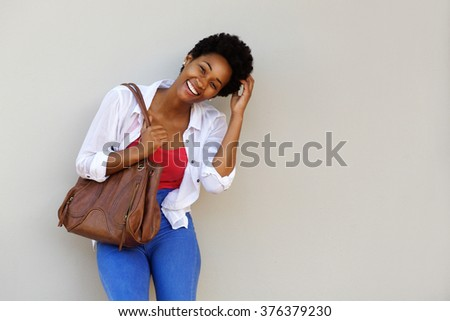 Portrait of smiling young african american woman carrying a bag standing against a wall - stock photo