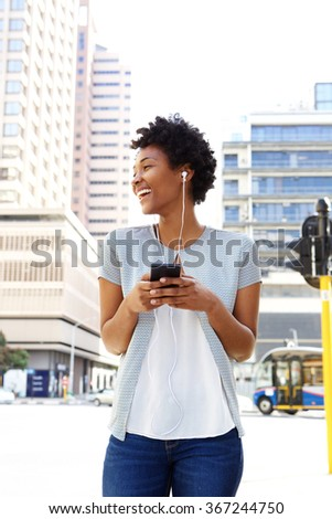 Portrait of smiling young african american woman listening to music on her mobile phone - stock photo