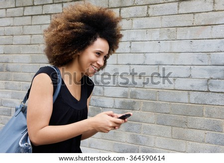 Portrait of smiling young african american woman walking with cellphone  - stock photo