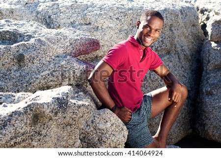Portrait of smiling young african guy sitting on the rocks at the beach - stock photo