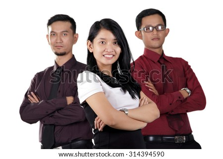 Portrait of smiling young Asian businesswoman posing with her two male colleagues on her back, standing with arms crossed, isolated over white background - stock photo