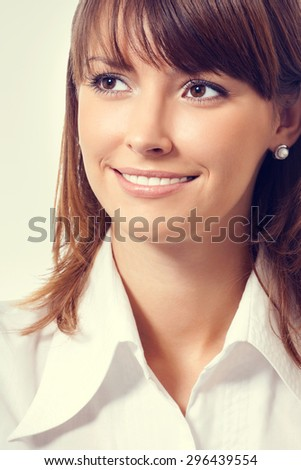 Portrait of smiling young attractive businesswoman in white business style clothing looking up or thinking - stock photo