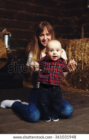 Portrait of smiling young beautiful woman playing with cute baby. Happy family concept. Rustic wooden background