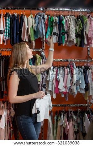 Portrait of smiling young beautiful woman shopping, standing in department store in front of rack with baby clothes, choosing new outfit for toddler child, holding hanger with cute white blouse - stock photo