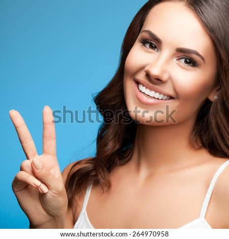 Portrait of smiling young beautiful woman showing two fingers or victory gesture, over blue background - stock photo