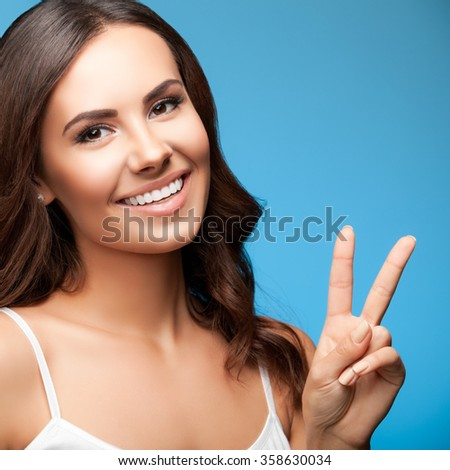 Portrait of smiling young beautiful woman showing two fingers or victory gesture, over blue background