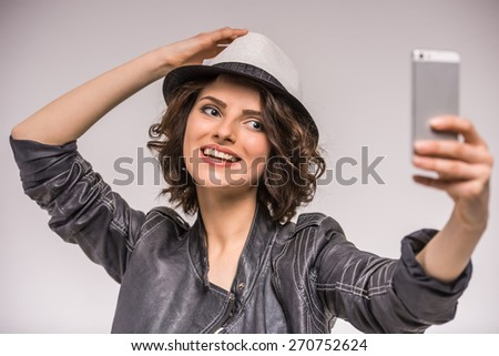 Portrait of smiling young beauty woman doing selfie on grey background. - stock photo