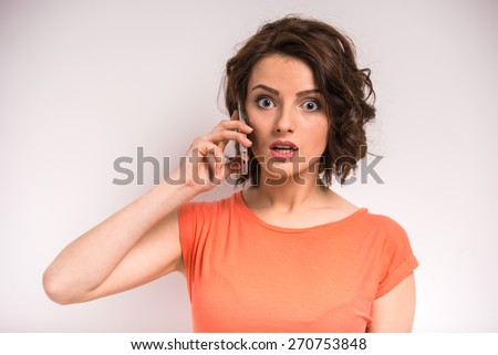 Portrait of smiling young beauty woman talking on the phone on grey background. - stock photo