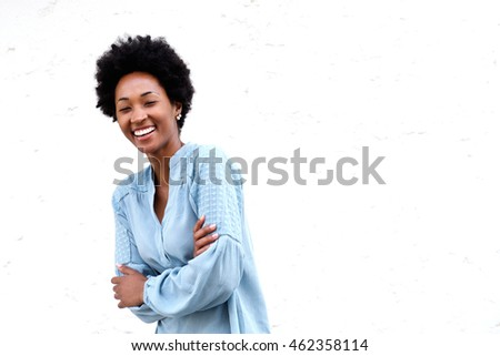 Portrait of smiling young black woman standing with her arms crossed against white background