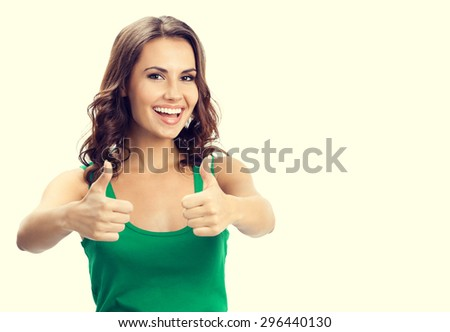 Portrait of smiling young brunette woman showing thumbs up gesture, in smart green casual clothing, with blank copyspace area for slogan or text message - stock photo