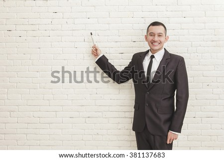 portrait of smiling young businessman looking at camera while pointing at copy space using marker