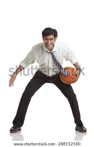 Portrait of smiling young businessman playing basketball - stock photo