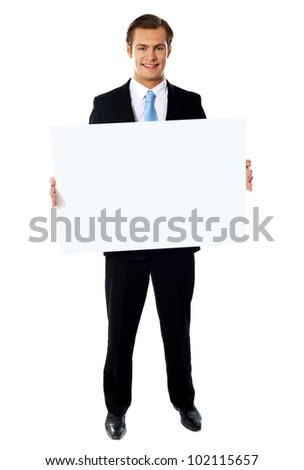 Portrait of smiling young businessman showing blank signboard