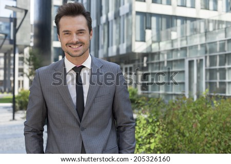 Portrait of smiling young businessman standing against office building - stock photo