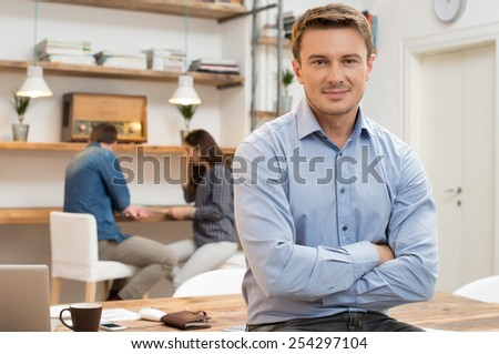 Portrait of smiling young businessman with armcrossed looking at camera in office - stock photo
