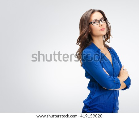 Portrait of smiling young businesswoman in glasses, against grey background, with blank copyspace area for slogan or text - stock photo