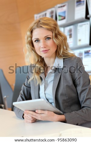 Portrait of smiling young businesswoman in office - stock photo