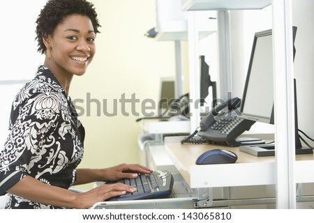 Portrait of smiling young businesswoman using computer in office - stock photo