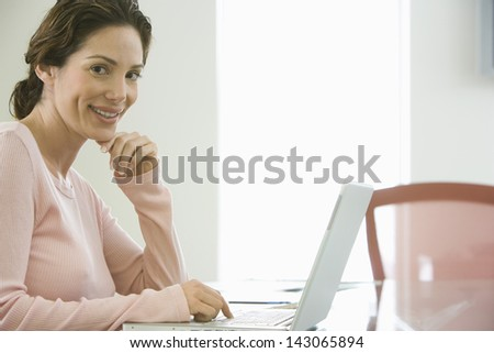 Portrait of smiling young businesswoman using laptop in conference room - stock photo