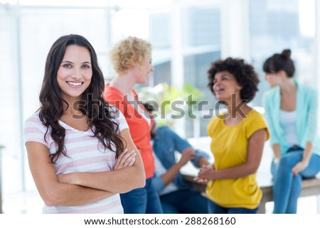 Portrait of smiling young businesswoman with colleagues in background at the office - stock photo