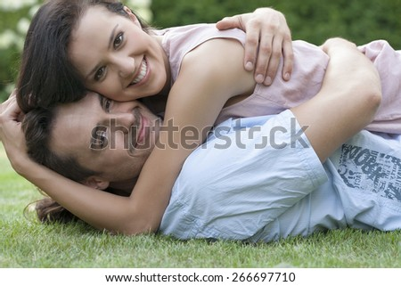 Portrait of smiling young couple embracing while lying in park - stock photo