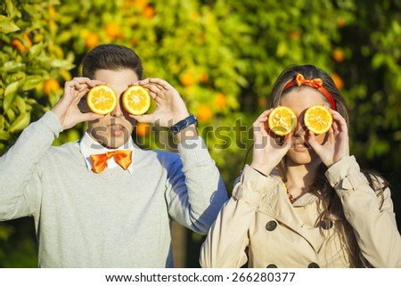 Portrait of smiling young couple holding oranges over eyes.