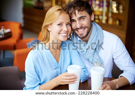 Portrait of smiling young couple in casual sitting in cafe - stock photo