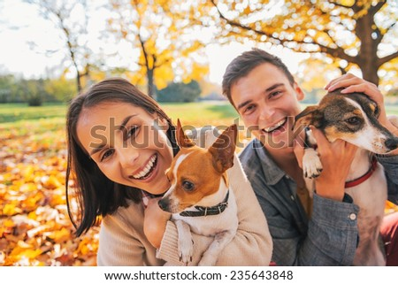 Portrait of smiling young couple with dogs outdoors in autumn park - stock photo