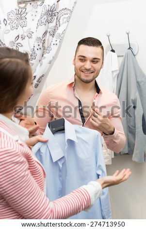 Portrait of smiling young couple with new apparel at fitting-room  - stock photo